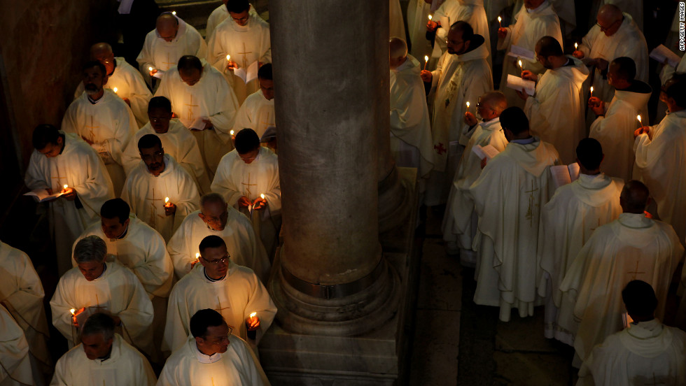 Roman Catholic clergymen hold candles as they circle the Stone of Anointing during the Holy Thursday Mass at the Church of the Holy Sepulchre in Jerusalem's Old City.