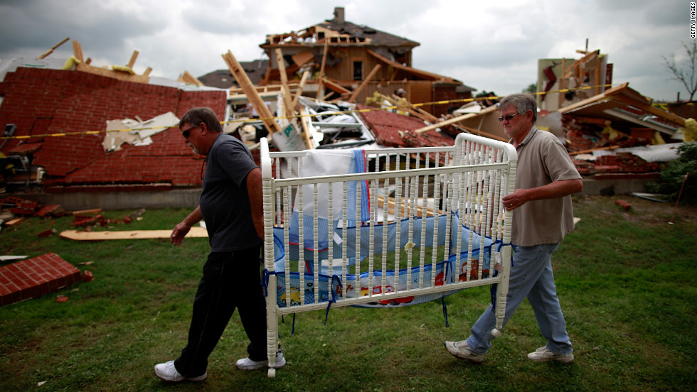 Mike Enochs, left, and Gary Enochs salvage a baby crib from Mike Enochs' destroyed home.  There are no reports of deaths so far, according to the mayors of Dallas and Arlington.