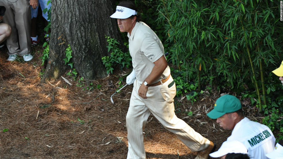 Phil Mickelson watches his shot from the rough at the fourth on the way to a triple bogey.