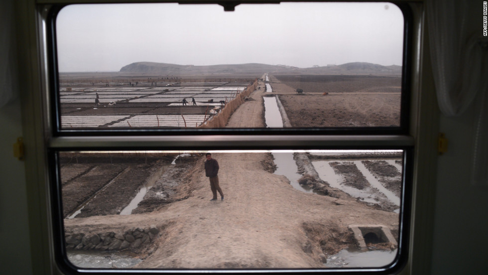 Workers and farms are seen through the window of a train as it passes through the country.