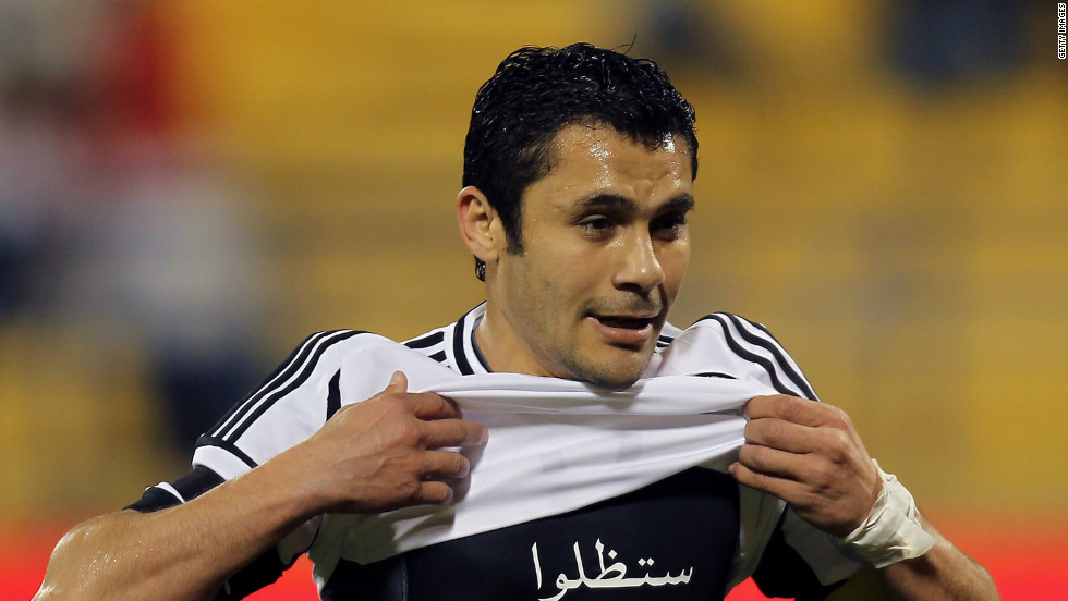 "Ahmed Hassan displays a shirt with the message ""You will remain in our hearts and we will never forget you"" in reference to victims of the Port Said tragedy. His former club Al-Ahly had played in the match against Al-Masry where fans rioted."