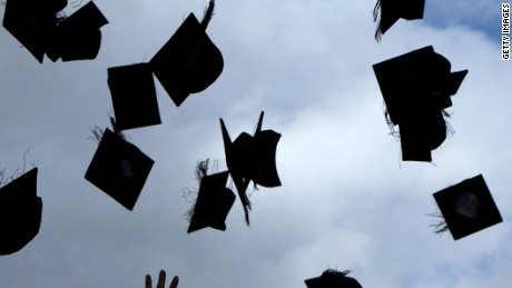 BIRMINGHAM, ENGLAND - JULY 14: Students throw their mortarboards in the air during their graduation photograph at the University of Birmingham degree congregations on July 14, 2009 in Birmingham, England.