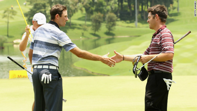 Louis Oosthuizen and Charl Scwartzel (left) shake hands at the end of the first round of the Malaysian Open.