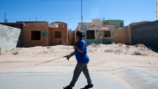 A woman walks past grafitti-covered houses in an abandoned neighborhood in Ciudad Juarez.