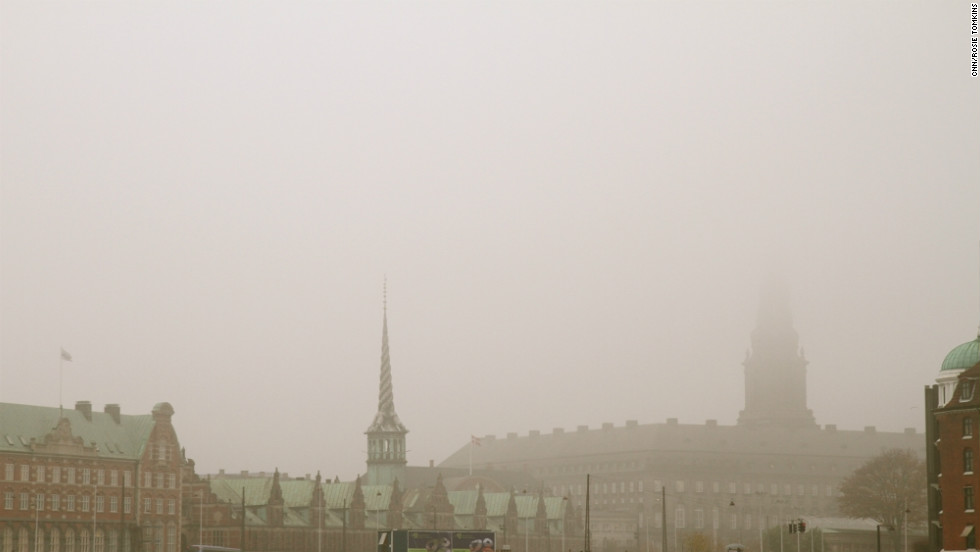 Mist shrouds the 17th-century spires of Copenhagen Harbor, a striking contrast to the sweltering streets of Mumbai.