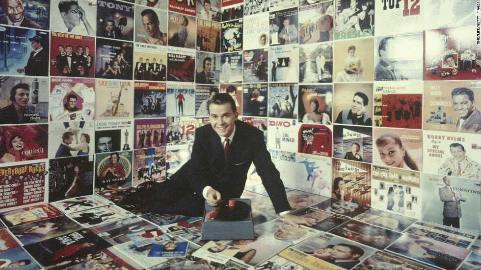 Clark sits in a room decorated floor to ceiling with record album covers circa 1958.