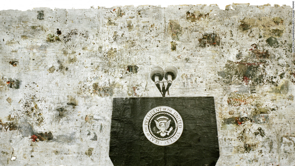 """Presidential Seal"" is seven meters long and 2.7 meters high, created by kennardphillipps in 2006. It is made of newspaper clippings with war photographs smashed on top with a hammer. The microphones on the empty presidential podium are pointing towards chaos and destruction, say the artists."