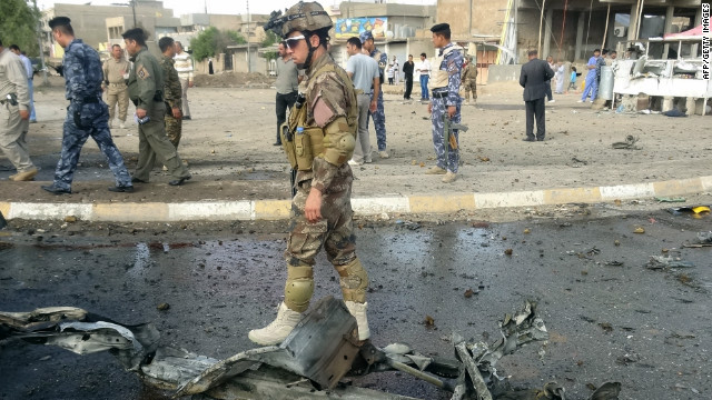 An Iraqi soldier walks past debris at the scene of two car bombs in the northern oil-rich city of Kirkuk on April 19, 2012.