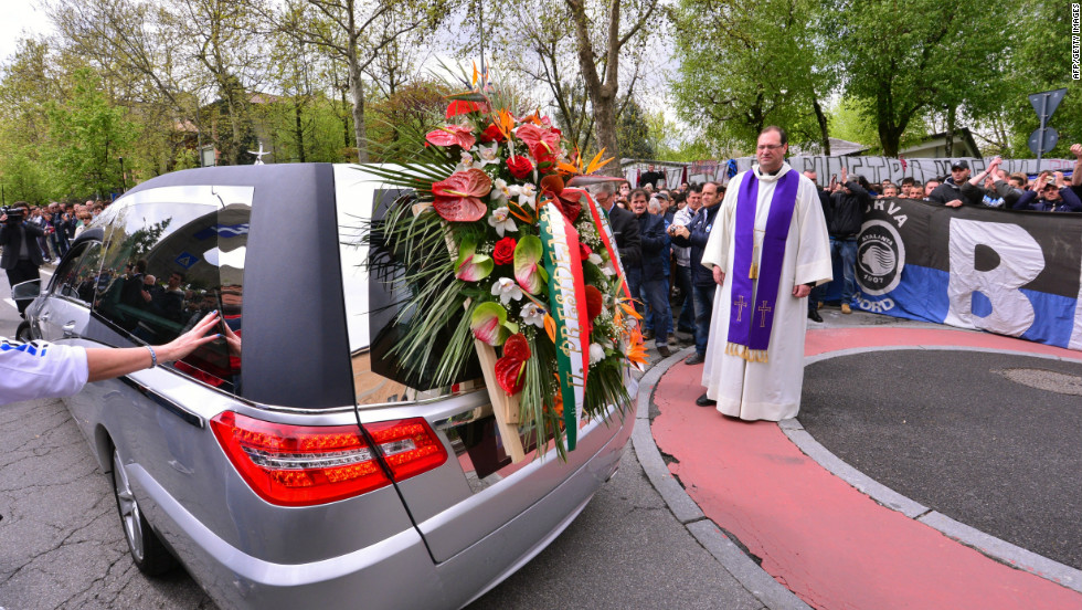 Priest Luciano Manenti watches the hearse carrying the coffin leaving after the funeral service.