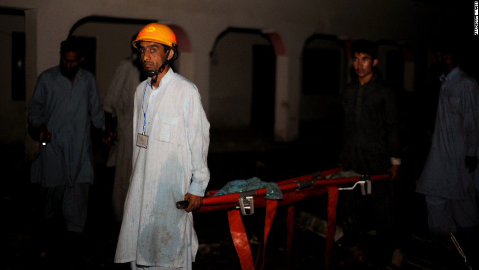 Pakistani rescue workers move a corpse in Hussain Abad.