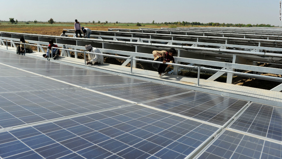 Workers put the finishing touches to India's first one megawatt canal-top solar power plant at Chandrasan village of Mehsana district near Ahmedabad.