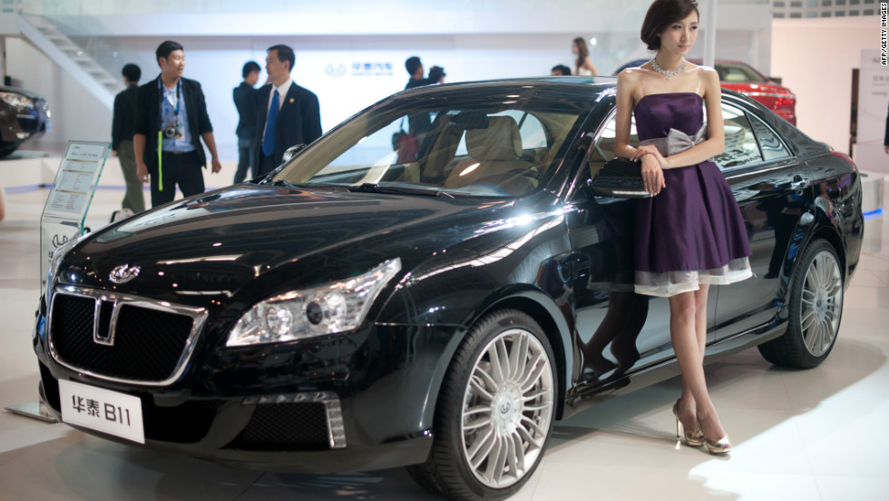 A model stands beside a 'B11' car by Chinese manufacturer Hawtai Motors, at the Auto China 2012 car show in Beijing.