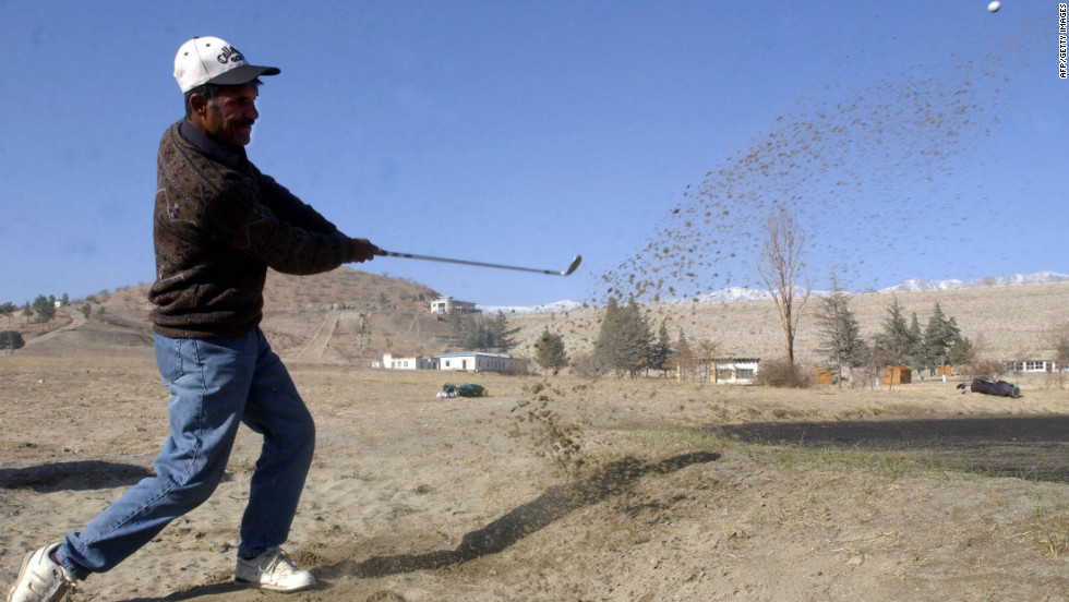 An Afghan player takes a shot during a tournament at the Kabul Golf Club. The nine-hole course, which first opened in 1967, became a battlefield in the 1990s when rival Mujahideen factions fought among themselves after overthrowing a Soviet-backed regime.