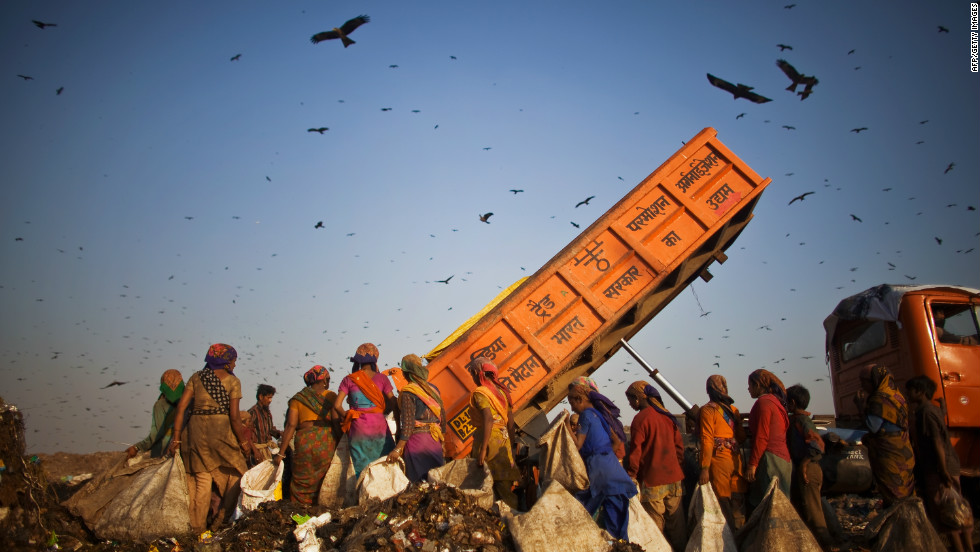 """Rag pickers"" wait as a truck delivers garbage at the 70-acre Ghazipur Landfill site. They will sort through it picking out recyclable materials to sell. Delhi is estimated to have between 80,000 and 100,000 rag pickers who remove around 1,200-1,500 tons of trash from the municipal disposal chain each day. These activities, carried out in an ad-hoc way have unfavourable environmental, occupational health and community health implications."