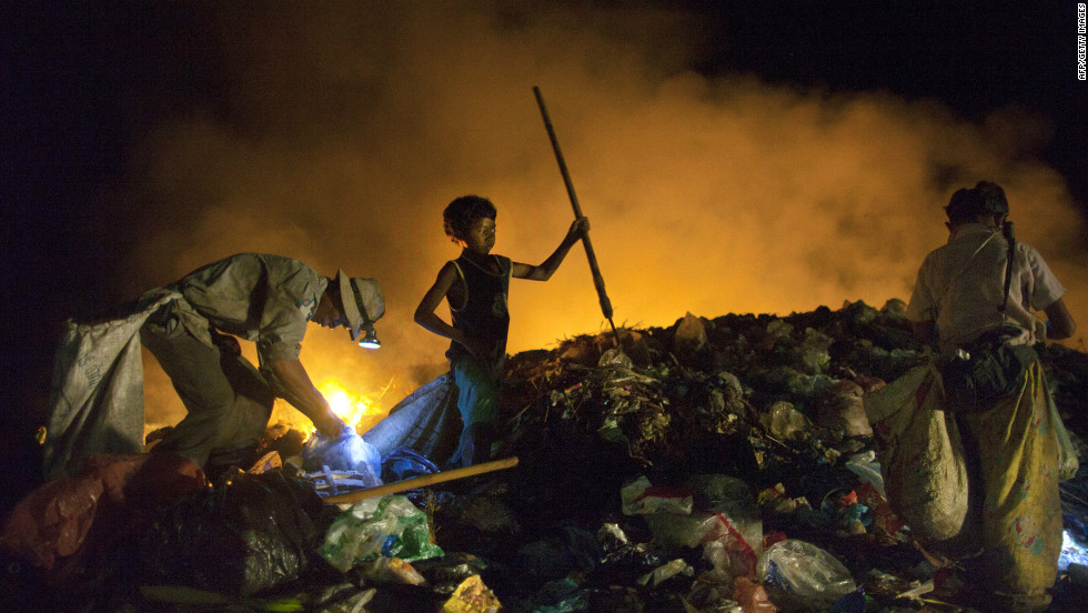 Cambodians work late into the night recycling garbage as fires burn at the local garbage dump. Many children work part time in the dump to help support their families while attending school during the day.