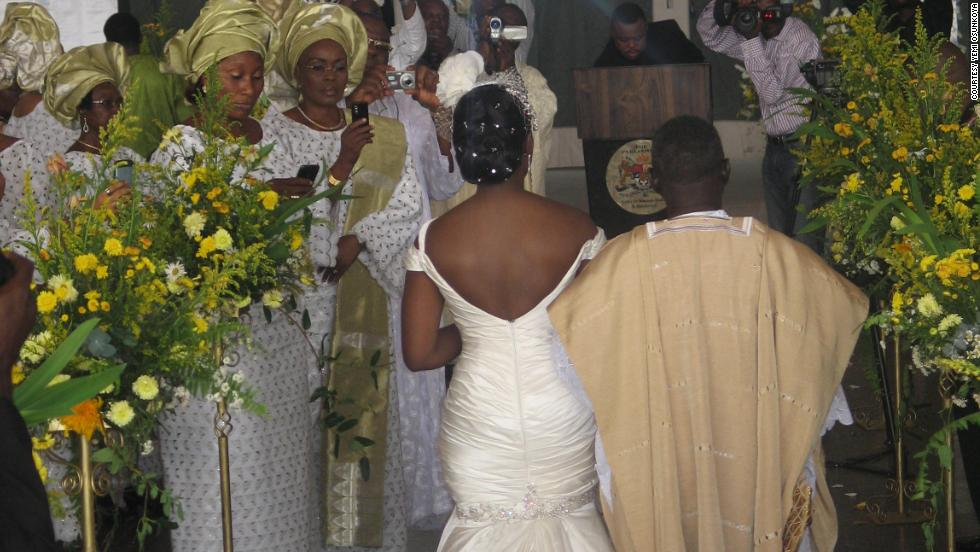 A Nigerian bride and her father make their way up the aisle, with the bride wearing a white gown and her dad in traditional attire.