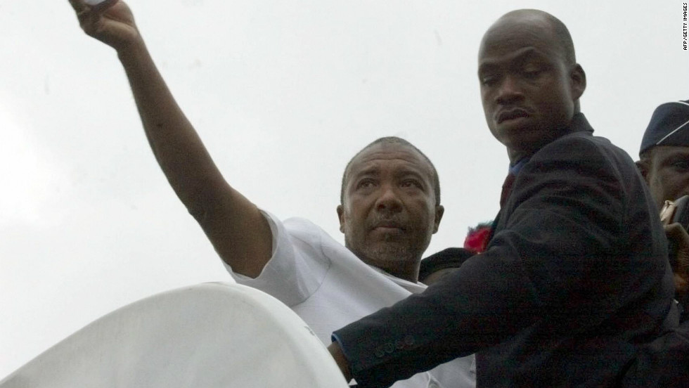Charles Taylor waves as he boards a Nigerian government plane in Liberia August 2003 that will take him into exile.