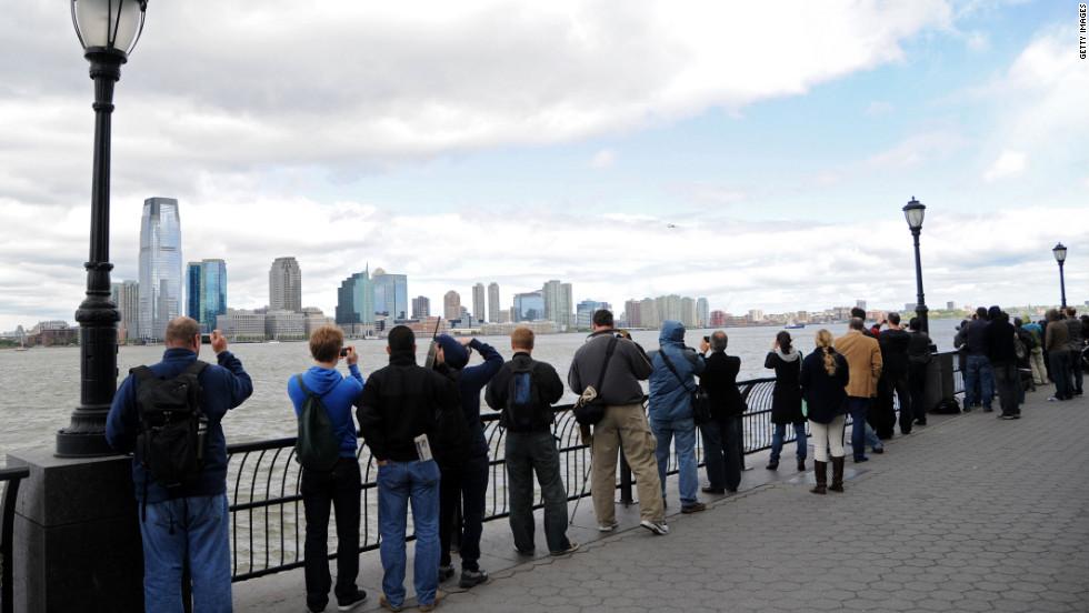 People watch the Enterprise space shuttle fly past the New Jersey skyline in its final flight.