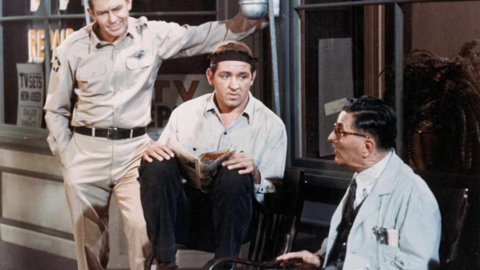 "Andy Griffith, left, Lindsey, center, and Howard McNear talk outside a barber shop in a still from ""The Andy Griffith Show"" around 1966."