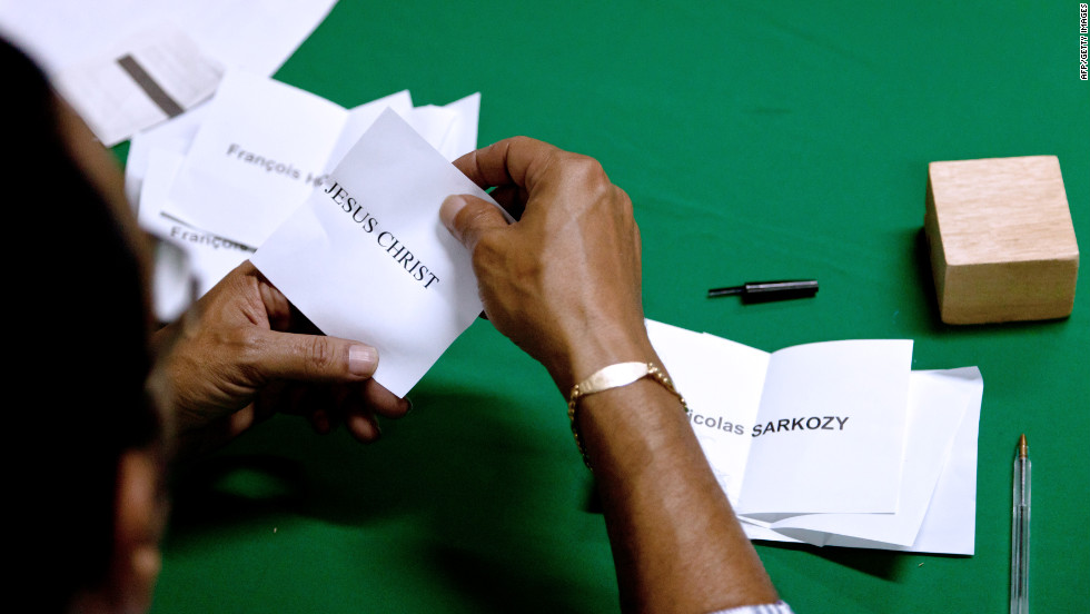"In South America, a scrutineer unfolds a ballot for ""Jesus Christ"" as he counts votes in French Guiana's Remire-Montjoly."