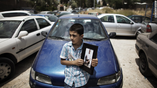 A Palestinian boy in Jerusalem holds a portrait Friday of a relative who's being held in an Israeli jail.