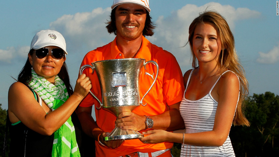 Fowler holds the Wells Fargo Championship trophy alongside his mother Lynne (letf) and girlfriend Alexandra Brown.