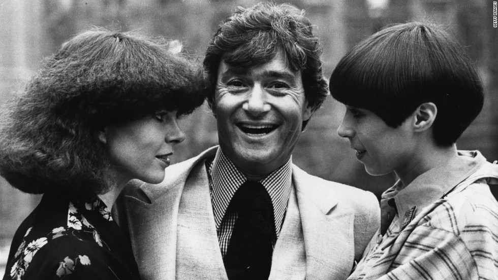 Vidal Sassoon stands between two contrasting examples of his hairdressing at a teach-in at the Albert Hall, where he returned to hairdressing after a five-year break in 1975.