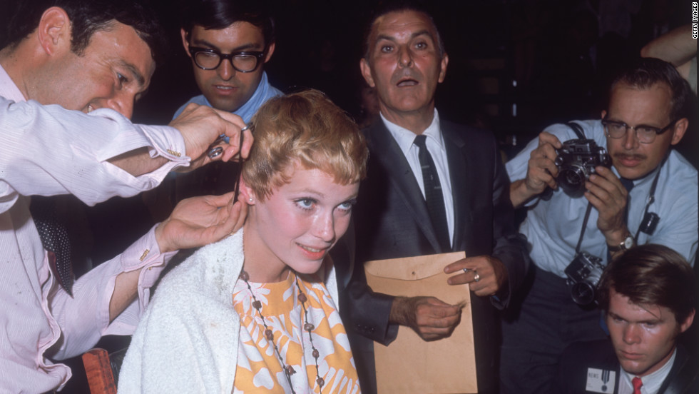 American actress Mia Farrow gets her hair cut short by Vidal Sassoon in 1967 while surrounded by photographers. Her famous pixie haircut was featured in the 1968 horror film Rosemary's Baby.