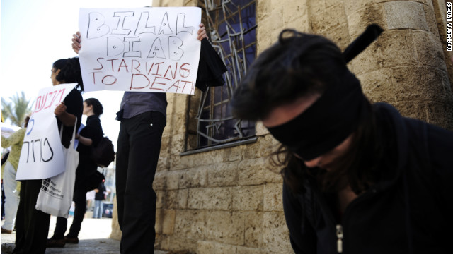 A blindfolded woman and demonstrators with posters show solidarity with prisoner Bilal Diab in Jaffa on Saturday.