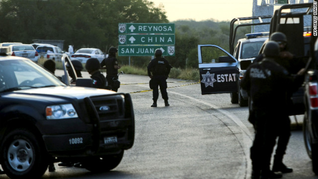 Mexican federal police block the road between Monterrey and Reynosa, where dozens of mutilated bodies were found Sunday.