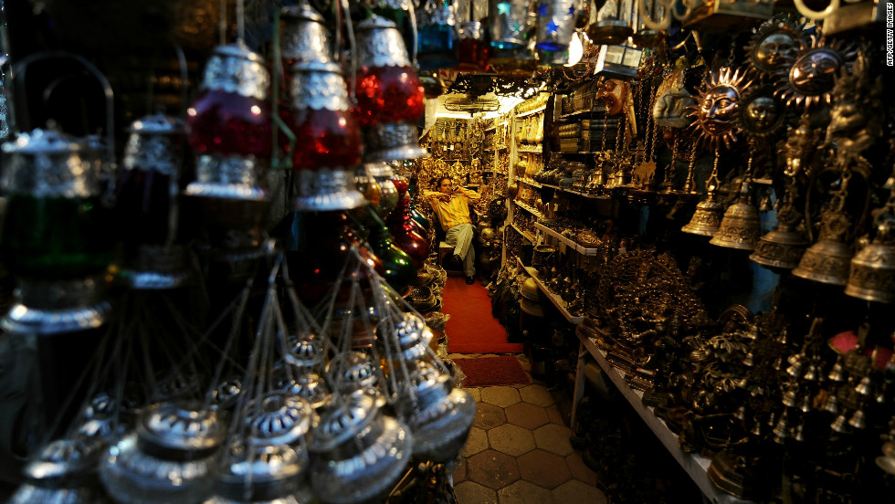 """An Indian shopkeeper waits for customers as he sells decorative goods at the popular Janpath street market. Popularly known as the """"Tibetan Market,"""" it's said you'll pick up a better selection of items (from antique locks to silver jewelry) at cheaper prices here than you will anywhere in Tibet itself."""