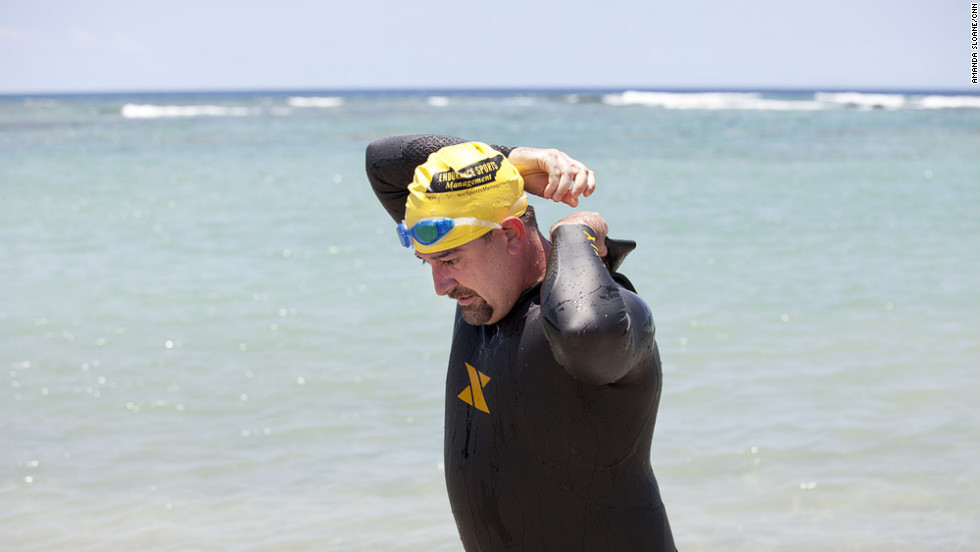 Morris attempts to take off his wetsuit while practicing the transition to biking.