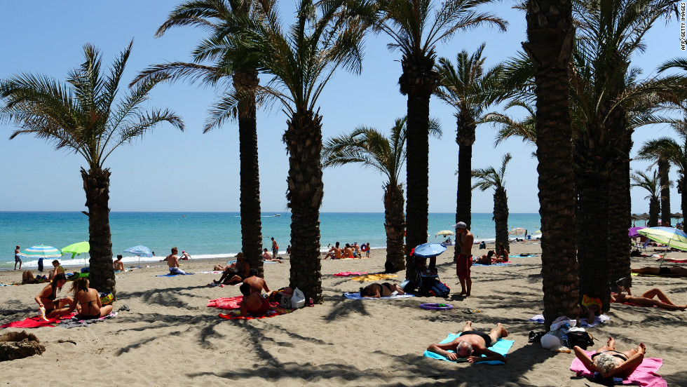 Tourists enjoy clear blue sky amid palm trees on an unusually quiet Costa del Sol Carihuela beach in Torremolinos, Spain in August 2009.