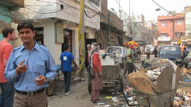 People on the tour walk through the congested, garbage-strewn streets of New Delhi.