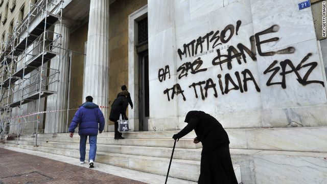 An elderly woman begs by the Bank of Greece headquarters in Athens on February 14, 2012.