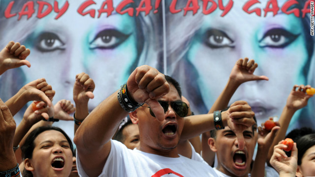 Members of Biblemode Youth Philippines protest in Manila Saturday in front of a banner showing Lady Gaga.