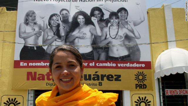 Mexican congressional candidate Natalia Juarez poses in front of a billboard on which she and other women are topless.