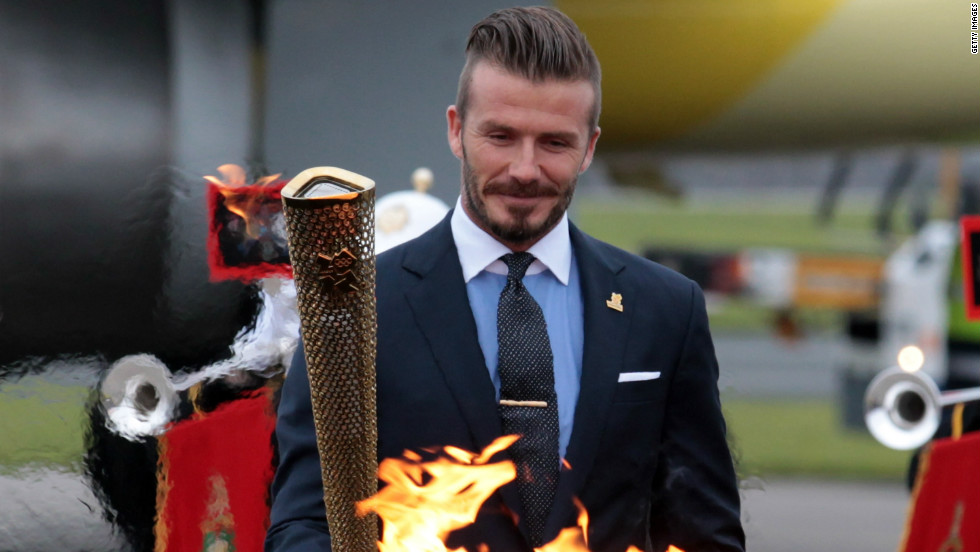 David Beckham lights the torch as it arrives at RNAS Culdrose airbase in Cornwall, England, on May 18. The footballer was part of a British delegation that flew back with the flame from Greece.