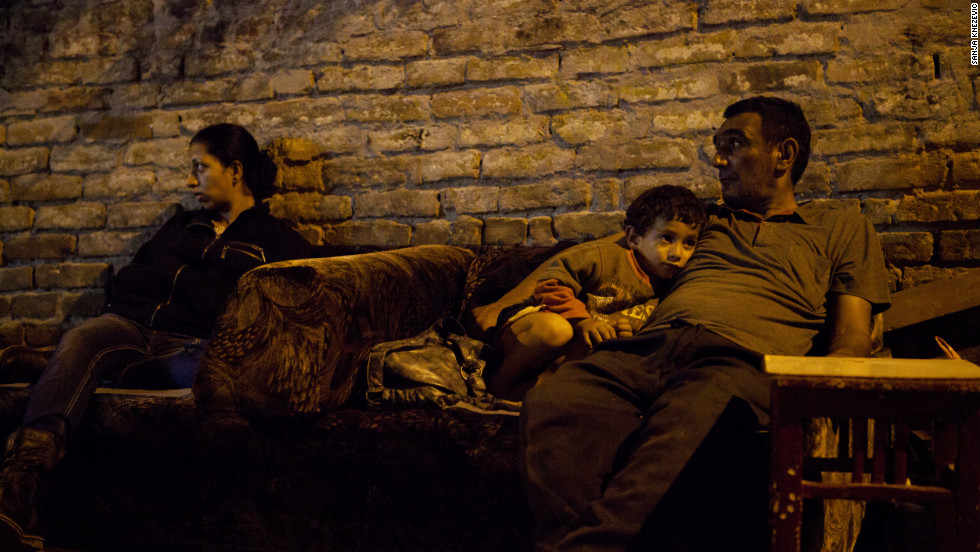 A woman, her neighbor and his son sit near the property they used to live in. They were forcibly evicted from Skadarska street settlement, Belgrade, Serbia, in August 2011 and ended up on the street.