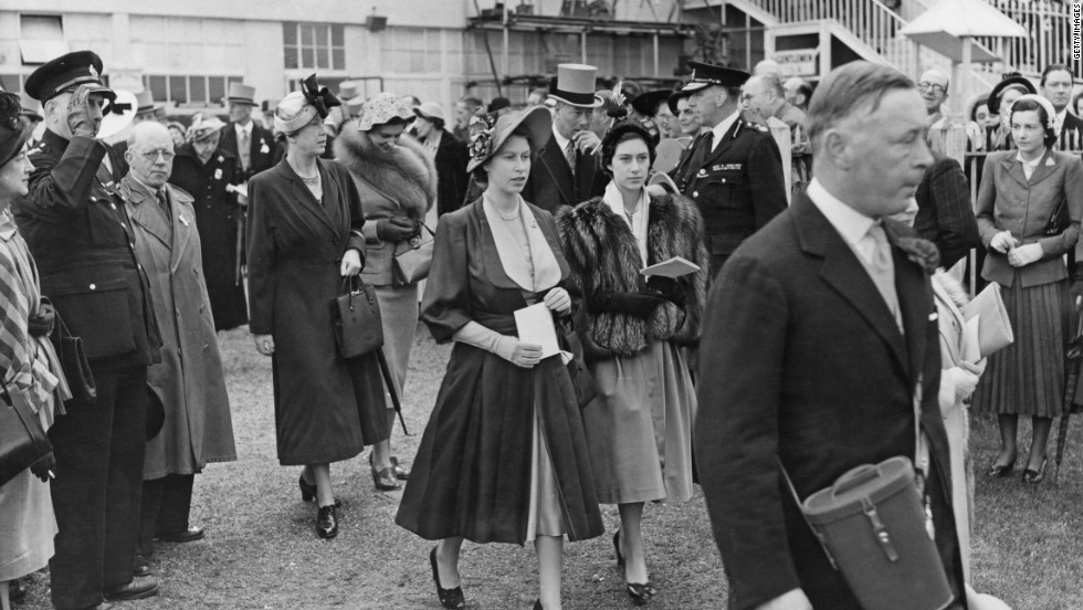 A fan of horse racing from a young age, then-Princess Elizabeth is seen walking through the paddock at the Epsom Downs racecourse during the derby on May 27, 1950. An appearance at Epsom Derby would be her first official engagement as queen several years later.