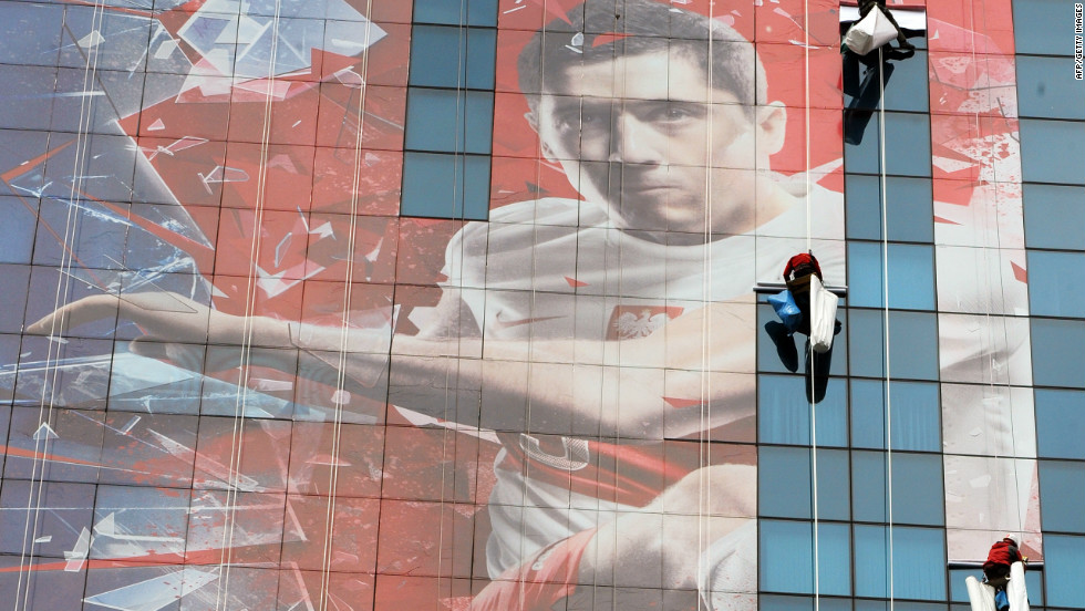Poland will co-host the 2012 European Championship with Ukraine. Here, workers unfurl a banner of Poland's Germany-based striker Robert Lewandowski. The national team has had little to cheer about in recent years and slumped to 75th in FIFA's world rankings, their lowest ever position. But it hasn't always been that way.