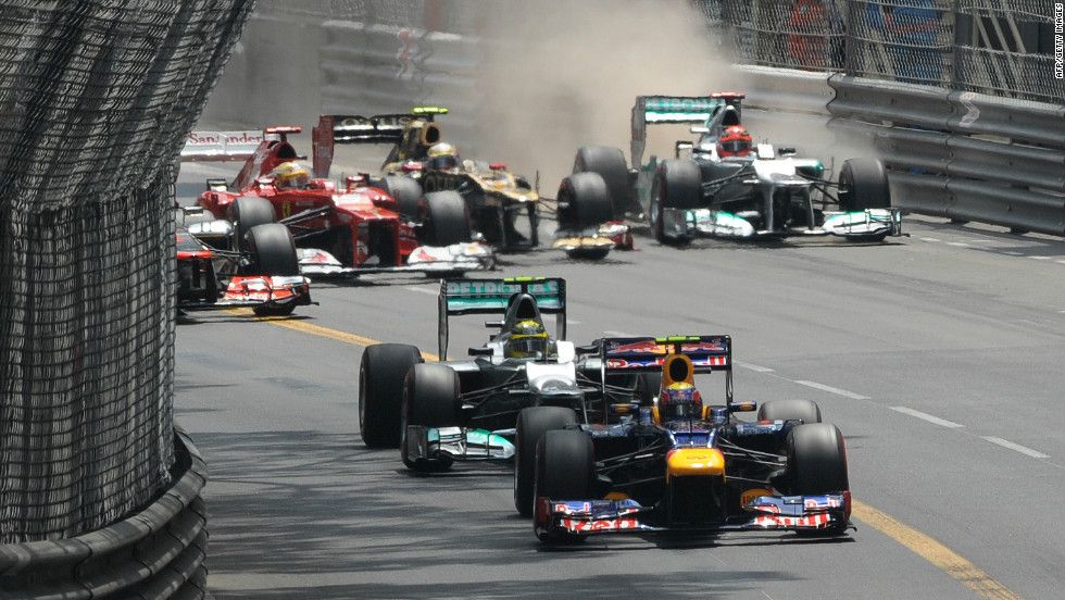 Red Bull driver Webber leads the way but behind him Romain Grosjean forces Michael Schumacher to go wide in an early clash.