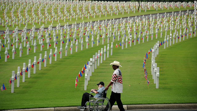 A man pushes an elderly man in a wheelchair among the graves of soldiers who fell during World War II at the Manila American Cemetery in Fort Bonifacio in the Philippine capital on May 27, 2012.