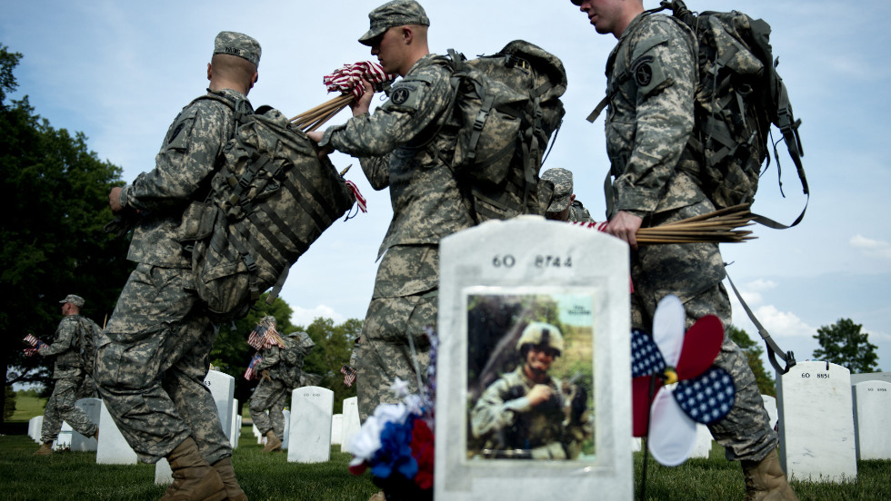 Soldiers at Arlington National Cemetery on Thursday pass the grave of U.S. Army Lt. Thomas Brown, who served in Iraq and died in 2008.