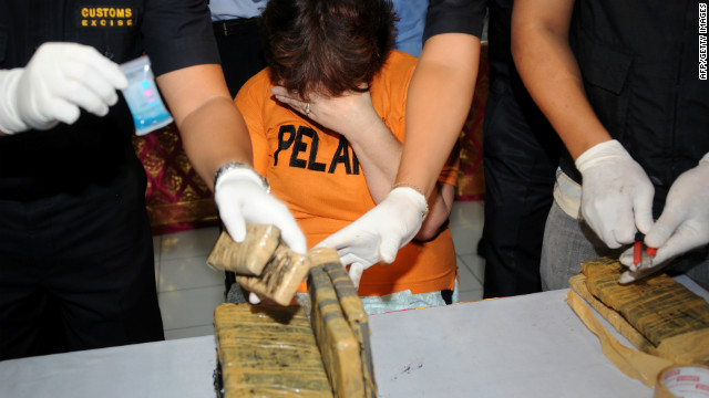 Briton Lindsay June Sandiford covers her face as officials display evidence at a customs office in Bali on May 28, 2012.