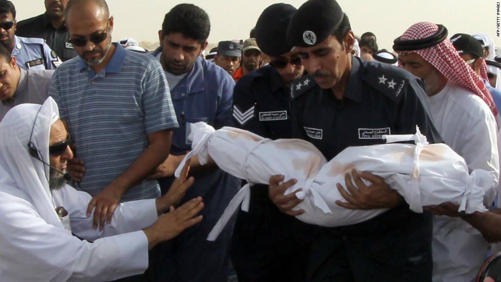 Members of the Qatari civil defense prepare to bury a child in Doha, Qatar, on Tuesday, May 29. A fire broke out at a shopping mall a day earlier, killing 19 people, including 13 children, officials said.