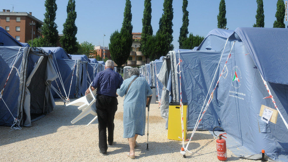 Elderly people walk in a temprorary emergency camp after the earthquake in Mirandola; the government declared a state of emergency in the quake area.
