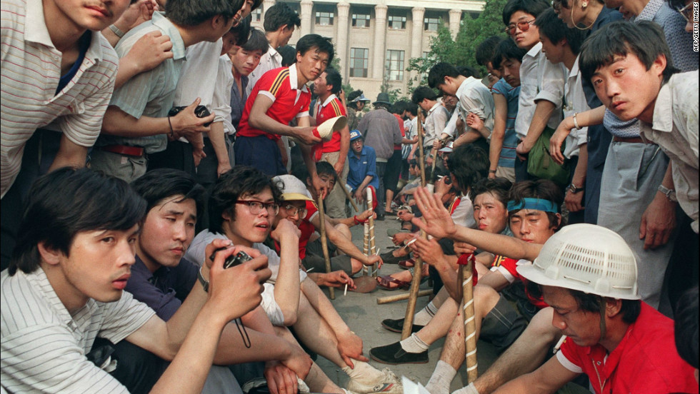 Beginning the night of June 3, 1989, and stretching into the early morning of June 4, Chinese troops used lethal force to end a seven-week-long occupation of Tiananmen Square by democracy protestors in Beijing.  In this photo, students and workers armed with wooden sticks gather outside the Great Hall of the People on June 3.