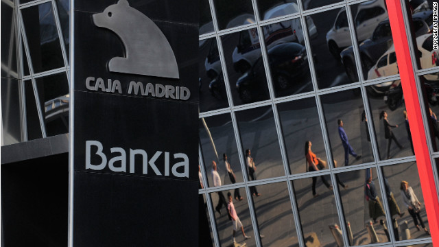 Commuters are reflected on the headquarters of Bankia SA on May 29, 2012 in Madrid, Spain.