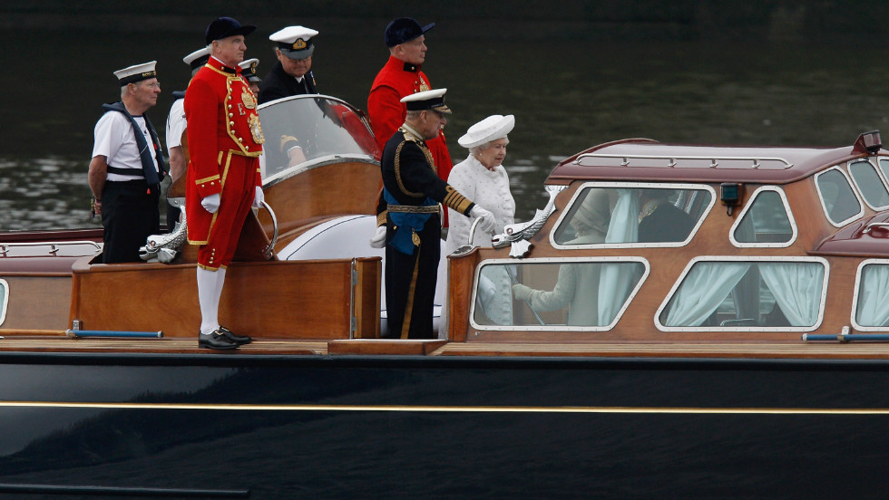 The queen and the Duke of Edinburgh leave the docks and head out on to the water to the beginning of the Thames River Pageant.
